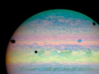 Tři Jupiterovy měsíce vrhající stín na obří planetu