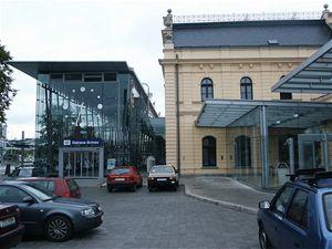 Na fotografii je vbočním pohledu patrná historická budova skovovým zábradlím, vlevo je skleněná přístavba a je také částečně vidět zastřešení vpřednádražním prostoru