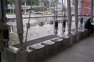Na fotografii vidíte pohled ze skleněné přístavby odbavovací haly na přednádraží prostor. Za sedačkami je mřížkou zakryté nasávání vzduchu ze vzduchové vrstvy nad hladinou vody dvou bazénů vodotrysku. Ty konstrukčně zasahují až pod mříž