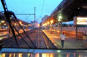 Výpravčí na Nádraží Praha Holešovice za špatných světelných podmínek dá pomocí svítilny se zeleným světlem soupravě jednotky 680 Pendolino volno