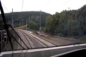 Ještě nedávno se vlaky proháněly na staré trati vpravo. Jízda na ní byla pro malé poloměry zatáček pomalá