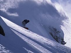 Snowboardista v terénu, v pozadí lavina