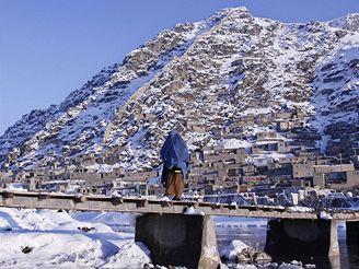 Žena v burce jde po mostě do Kábulu.
