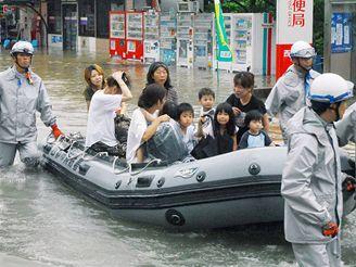 Hasiči odvážejí obyvatele zaplavených oblastí na člunech do bezpečí.
