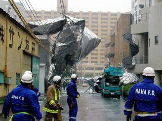 Hasiči ve městě Naha odklízejí obří plechovou střechu, kterou vzal vítr.