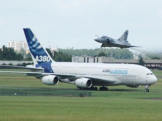 Francouzský vojenský letoun Mirage 2000 vzlétá přes pojíždějící dopravní letadlo A380