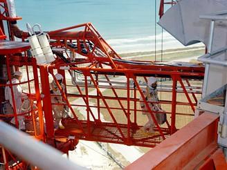 Kosmonauti přecházejí můstkem z obslužné věže do své kabiny