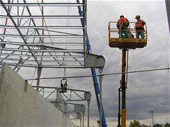 Vysokozdvižná plošina se blíží k čepu kontrukce těsně před jejím usazením