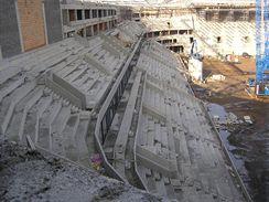 Západní tribuna s budoucími VIP lóžemi a severní tribuna, která ukrývá hotelovou část stadionu