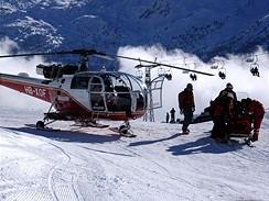 Záchranáři ošetřují zraněného lyžaře na sjezdovce - ilustrační foto