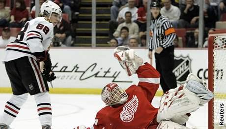 Dominik Hašek (v červeném) z Detroitu vyráží střelu Patrick Kanea z Chicaga.