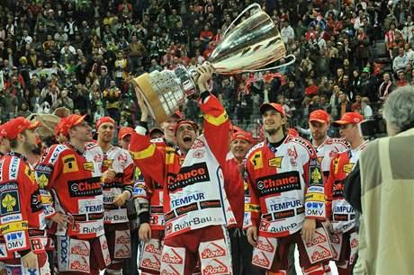 Michal Vondrka drží nad hlavou pohár pro hokejové mistry. Titul vybojovala Slavia