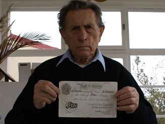 Adolf Burger drží v ruce falešnou librovou bankovku