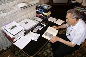 Adolf Burger ve své pracovně listuje prvním vydáním své knihy o zážitcích z koncentračního tábora
