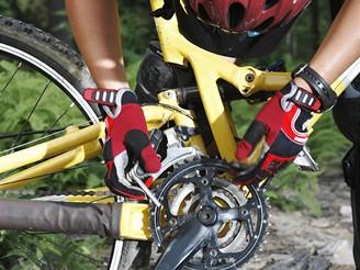 Cyklista upravuje řetěz na kole