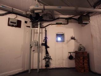 Střílna k ochraně hlavních zbraní levé střelecké místnosti. Vlevo ventilátor k odsávání zplodin ze zvonu, dále LK vz. 26-pod ním lafeta, vpravo pozorovací průzor, bedýnky s municí, granátový skluz a stěnový periskop