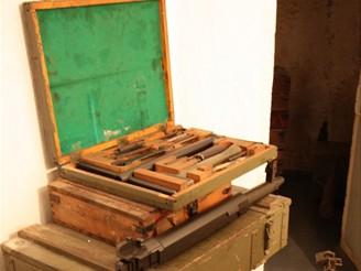 Vlevo na bedýnkách potřeby pro TK vz. 37, dále těžká hlaveň, pěchotní lafeta a plnička kulometných pásů