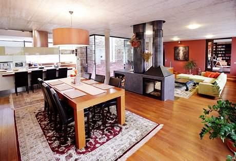 Dřevěná podlaha, výrazné teplé barvy stěn a pohledový beton na stropě tvoří vyváženou kombinaci