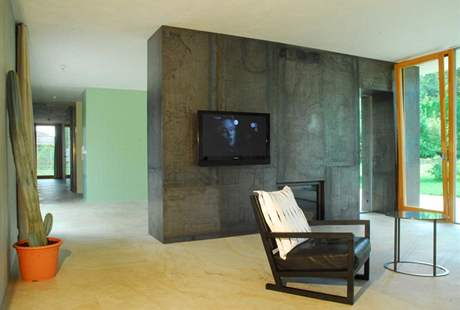 Stěna s krbem a vestavěnými skříněmi je obložena patinující ocelí Corten