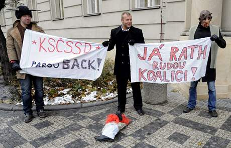 Demonstranti transparenty vyjadřují nesouhlas s jednáním Davida Ratha s komunisty o podpoře v novém středočeském zastupitelstvu