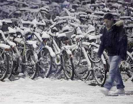 Mladík v curychu prochází kolem bicyklů pokrytých sněhem