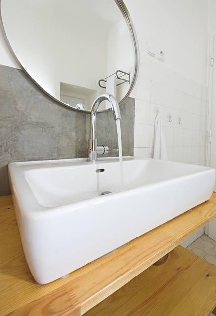 Cementová pálená omítka je výborným pozadím pro jednoduché tvary umyvadla i vodovodní baterie