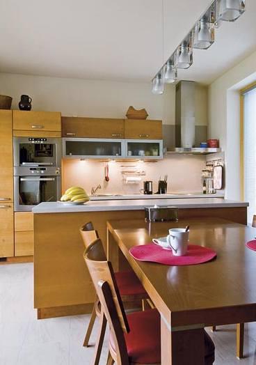 Jídelní stůl přisazený k ostrůvkové skříňce je z kuchyně snadno přehlédnutelný