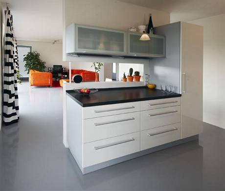 Kuchyně je oddělena a zároveň propopjena s obývacím pokojem pomocí horizontálního výřezu v dělící příčce