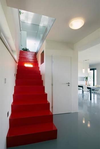 Železobetonové schodiště představuje díky červenému nátěru barevnou dominantu interiéru
