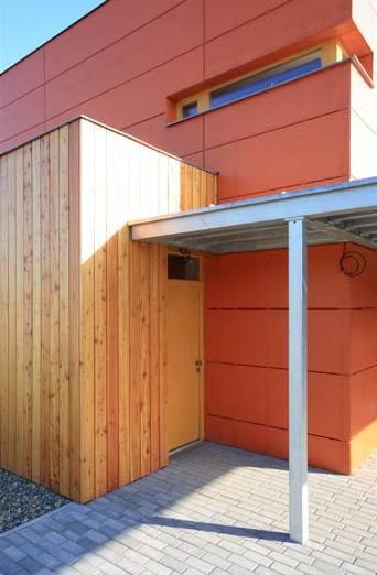 Vstup do domu chrání lehká dřevěná stříška přímo navazující na kryté stání pro auto