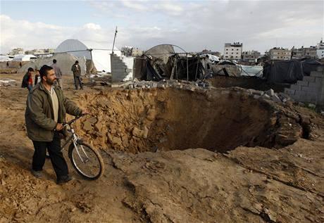 Palestinec obchází kráter po vybombardovaném tunelu v pásmu Gazy