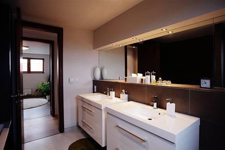 Bílé lesklé skříňky v kombinaci s velkoformátovými tmavými obklady a velkým zrcadlem působí velmi elegatně