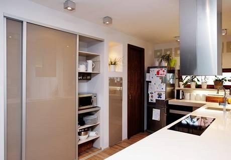 Za posuvnými dveřmi se skrývají zapuštěné police na nádobí i drobné spotřebiče