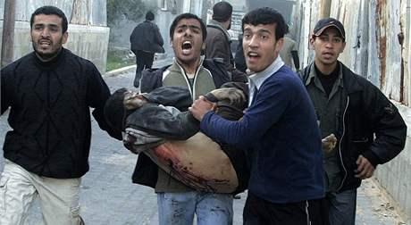 Palestinci odnášejí zraněného ze školy OSN v pásmu Gazy.
