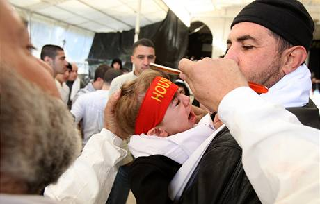 Muž v Libanonu poklepává během oslav svátku ašúra, který slaví šíité, hlavu dítěte břitvou. (7. ledna 2008)