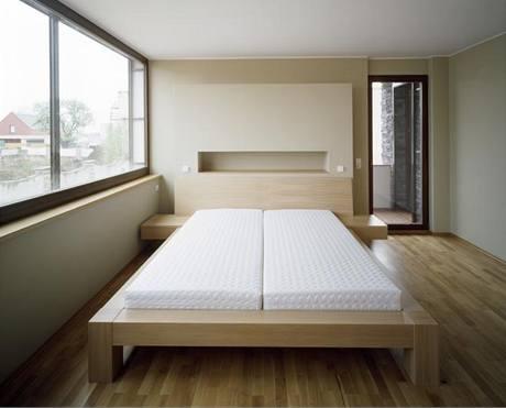 Ložnice rodiče je zařízena nábytkovou sestavou na zakázku z dubové dýhy
