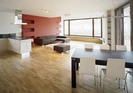 Obývacímu pokoji dominují matně červená stěna s rohovými nikami na knihy. a jídelní stůl s dýhou wengé