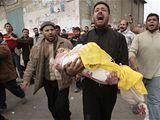 Palestinec nese při pohřbu tělo malé holčičky, která zemřela při izraelském útoku.