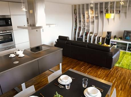Obývací místnost s integrovanou kuchyní je sjednocena hnědo-šedou barevností