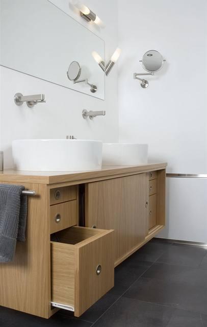 Závěsná skříňka z dubové dýhy vyrobená na zakázku (Matějka-Štofa) nabízí úložný prostor na kosmetiku, ale i koš na prádlo