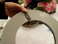 Pomocí oboustranné lepicí pásky se namočený věnec z aranovací hmoty přichytí na podložku.
