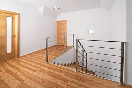 Schodiště do patra má jednoduché kovové zábradlí, ale dřevěné stupnice