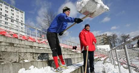 Fotbalisté 1. FC Brno uklízí sníh ze sedaček stadionu na Srbské