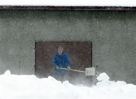 Muž ze Sedliště odklízí nové přívaly sněhu. (11. února 2009)
