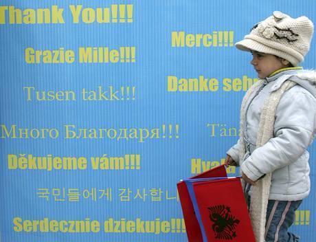 Dívka prochází kolem transparentu, kde Kosovo děkuje všem státům, které ho uznaly