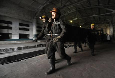 Záchranáři odnášejí tělo jedné z obětí výbuchu v čínském dole. (22. února 2009)