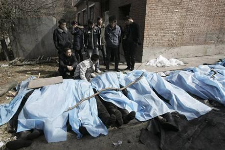 Příbuzní truchlí nad těly obětí výbuchu v čínském dole. (22. února 2009)