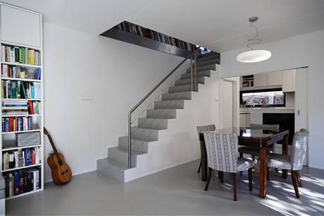 Jednoduché schodiště se subtilním nerezovým zábradlím pomáhá vymezit prostor jídelny a obývacího pokoje
