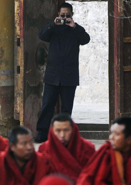 Tibetsk� mnichy na ka�d�m kroku hl�daj� policist� v civilu (na pozad�)