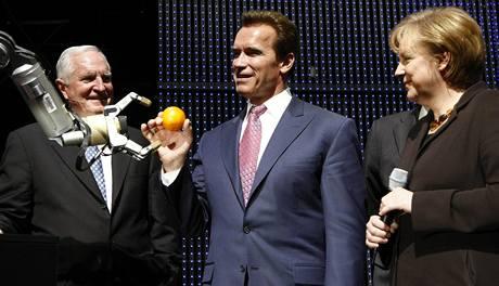 Robot Marvin podává Arnoldu Schwarzeneggerovi pomeranč, vpravo přihlíží německá kancléřka Angela Merkelová (vlevo je šéf firmy Intel)
